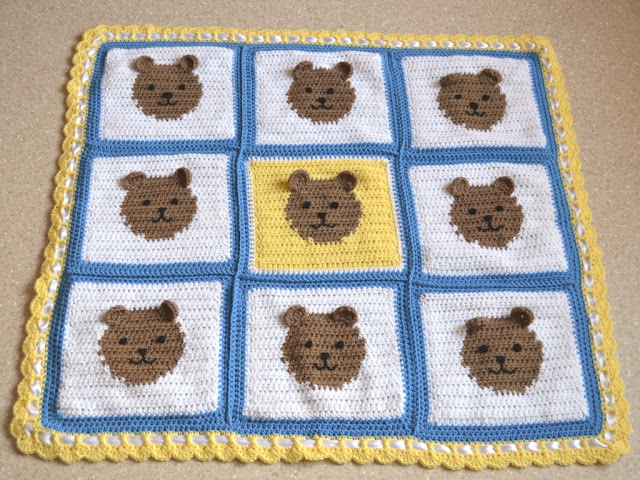 A square baby blanket comprised of 9 squares, all white except for the centre square which is yellow. Each square has a blue border and a tan teddy bear face in the middle. The teddies have three dimensional ears stitched onto the surface of the blanket. The outside border of the blanket is crocheted in yellow with a row of filet crochet and ending with a scalloped edge. White satin ribbon is woven through the filet spaces.
