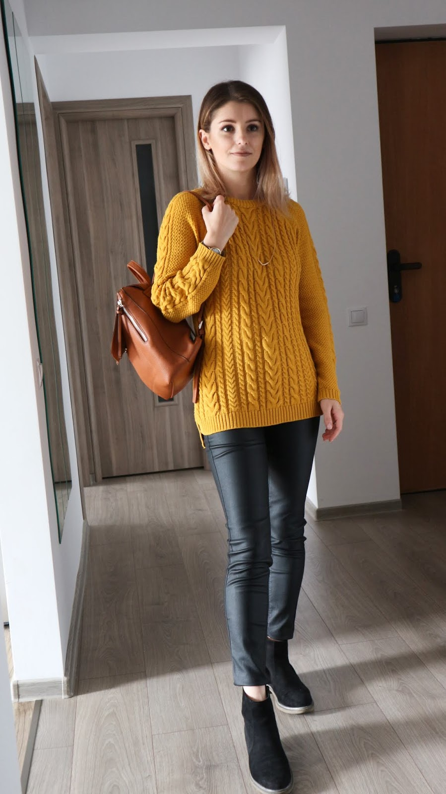 mustard sweater and coated jeans outfit