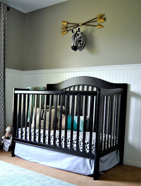 Nursery, Boy Nursery, Black Crib, Gallery Wall, Faux Taxidermy, Faux Elephant Head, Adventure Themed Nursery, Safari Theme, Neutral Nursery, Black and White, Zebra Head, Black Crib, Board and Batten, Curtains, Trellis, Bead Board, Arrows, Pouf, Rocking Chair, Vintage, Black Dresser, Brass Hardware, Vintage Dresser, Rug, Rugsusa, Rugs Direct, Blue Rug, Mint, Mint Nursery, Turquoise, Blue Nursery, Boy Nursery, Gender Neutral Nursery