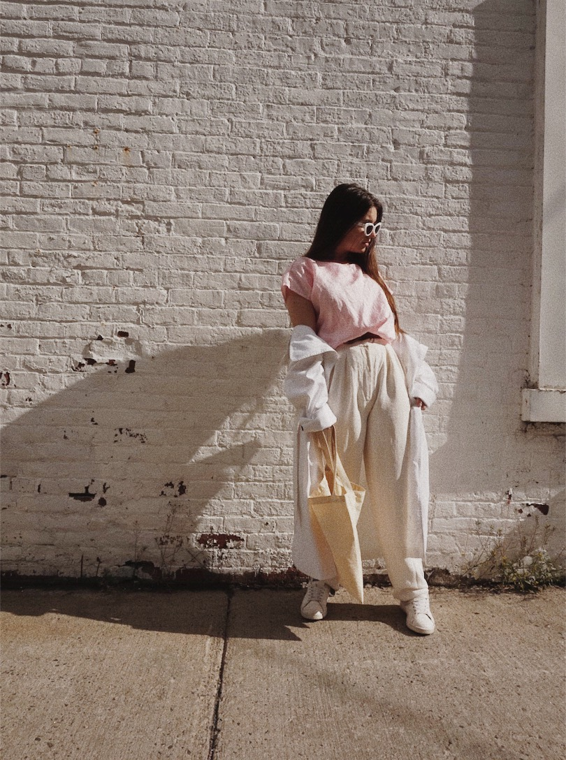 girl wearing thrifted outfit, pink shirt, sunglasses, white pants