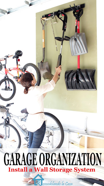 Cristina Garay hanging tools on wall organization system.