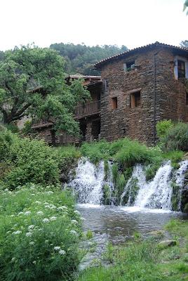 Vista de la pequeña cascada sobre la que se levantan las casas de piedra de Robledillo de Gata