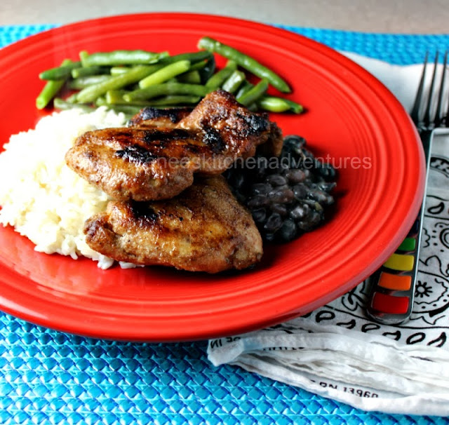 Grilled Jerk Chicken Thighs by Renee's Kitchen Adventures on a red plate with white rice, black beans, and green beans. A fork is next to the red plate.