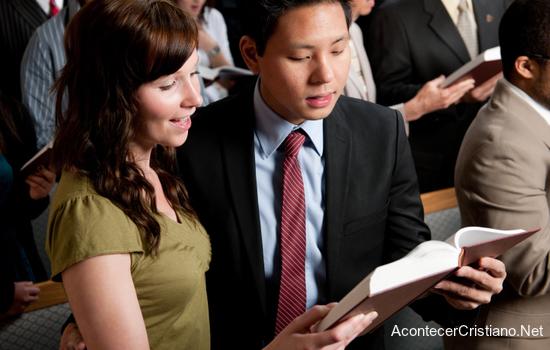 Pareja feliz leyendo la Biblia juntos en iglesia