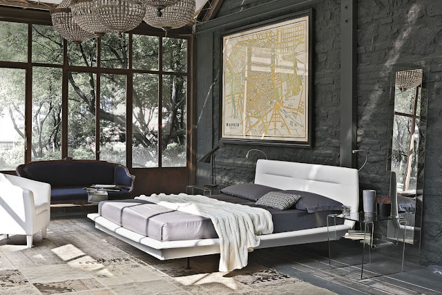 Floored on a newspaper rug, this charcoal-painted brick wall provides a strong background for an industrial style bedroom