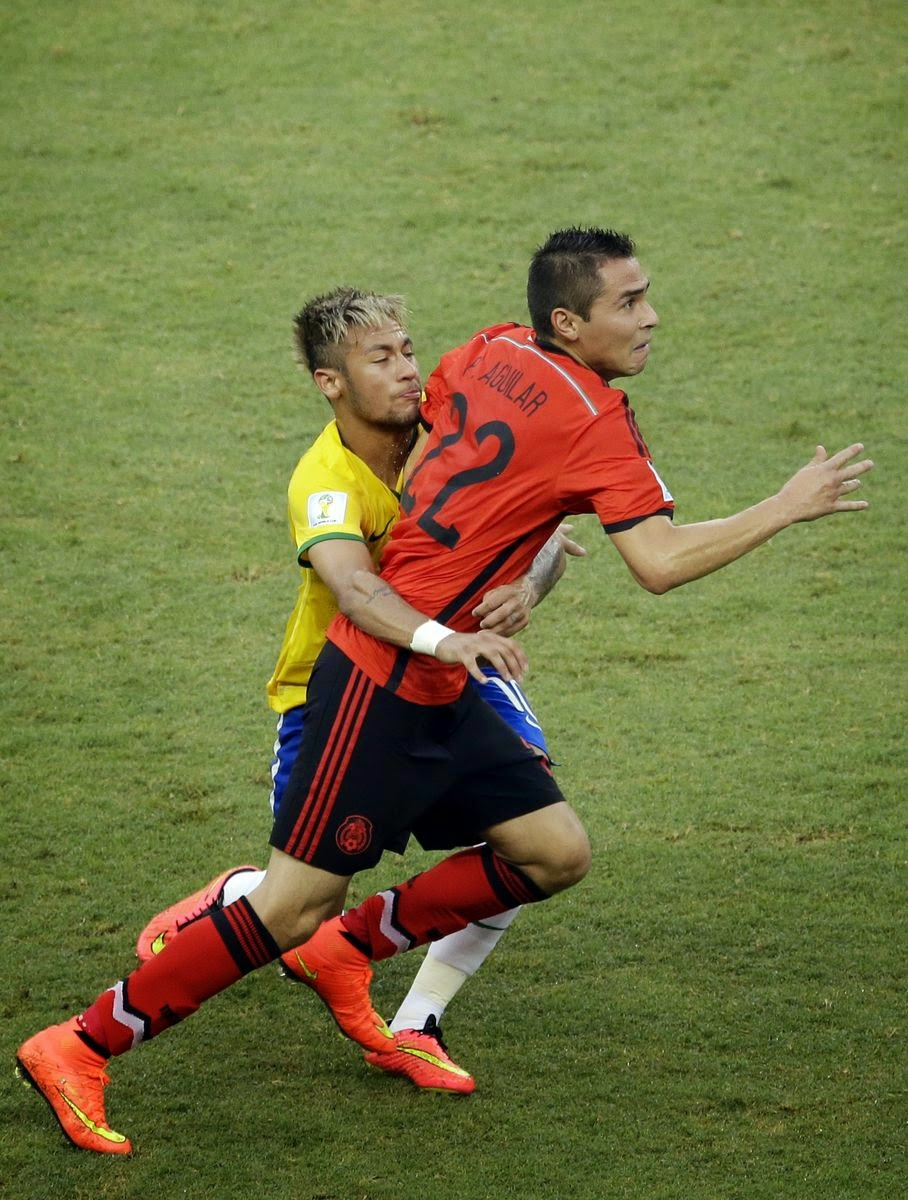 Brazil's Neymar, left, holds Mexico's Paul Aguilar during the group A World Cup soccer match between Brazil and Mexico at the Arena Castelao in Fortaleza, Brazil, Tuesday, June 17, 2014.