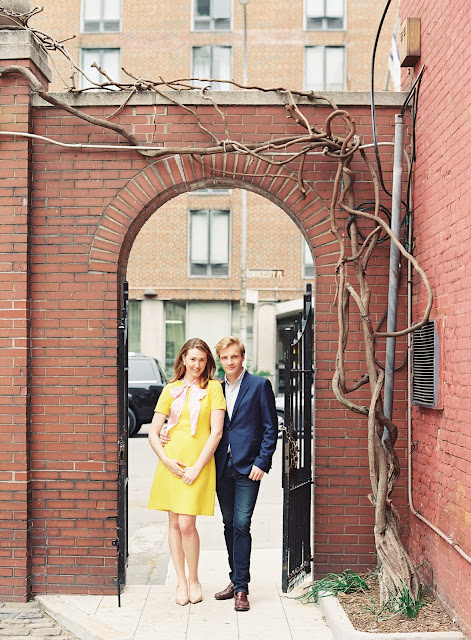 Liz and Ted celebrate their engagement under a red brick archway in NYC