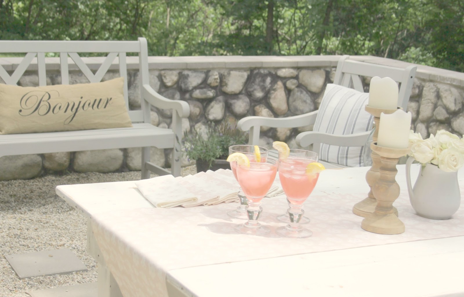 Pink lemonade on white farm table in pea gravel courtyard - Hello Lovely Studio