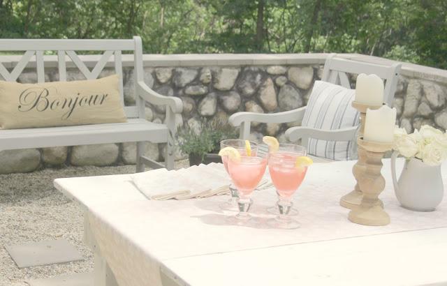 Pink lemonade on white farm table in pea gravel courtyard - Hello Lovely Studio