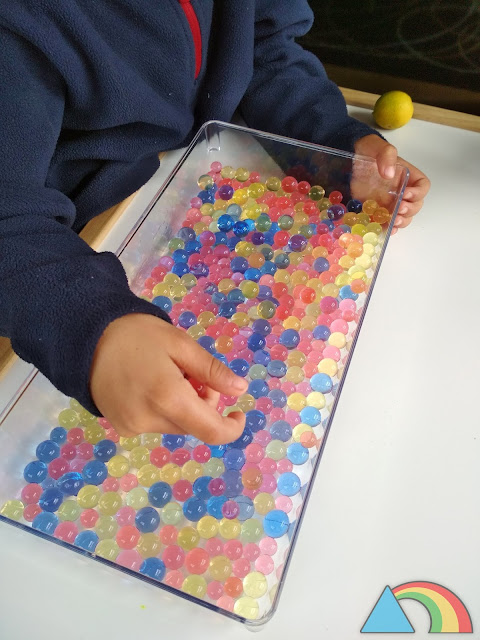 Niño manipulando bolas de gel o water beads de colores.