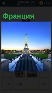 Вдали Эйфелевая башня символ Франции на фоне города и голубого неба