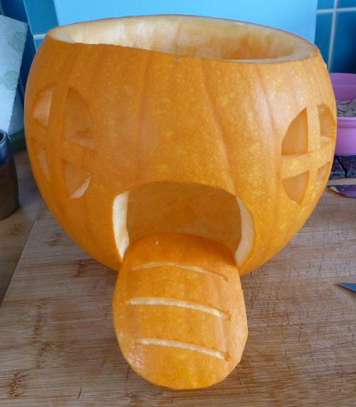 Orange pumpkin with door and windows carved into it