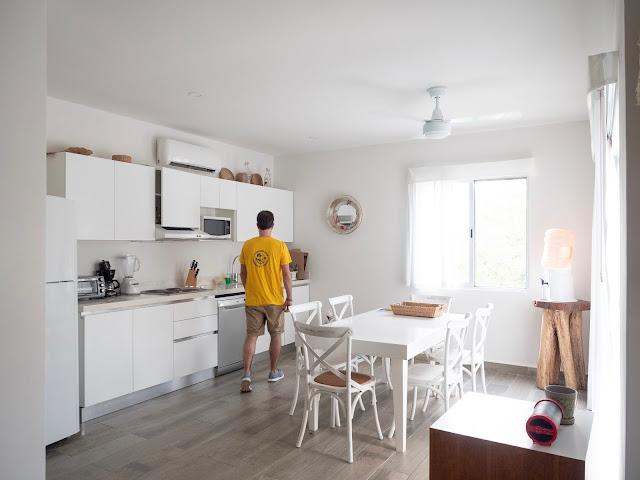 Hombre de espaldas con camiseta amarilla en una cocina muy blanca y luminosa