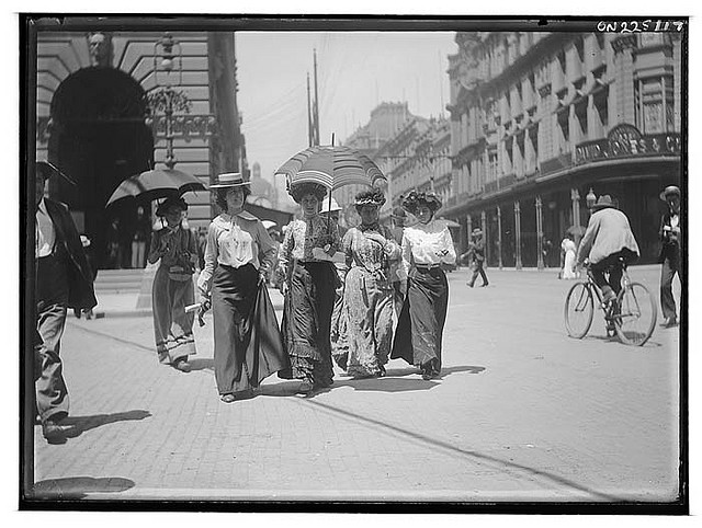 [Pedestrians on George St], ca. 1900, from Frederick Danvers Power : photonegatives, 1898-1926 / Frederick Danvers. Power Notes: Amateur photographer Frederick Danvers Power had a concealed detective camera, which he used to snap these women crossing Martin Place at George Street, with the Post Office behind them. This image gives us a more accurate idea of what women actually wore, than formal studio photographs or magazine illustrations. People wore their best outfit to the portrait studio and parasols and hats, which shaded the face, were not permitted. On the other hand, the idealised renditions of fashion published in magazines show neither creased clothes nor worn shoes.