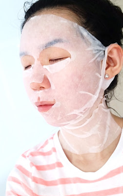 Michelle's sheet mask selfie, side view.