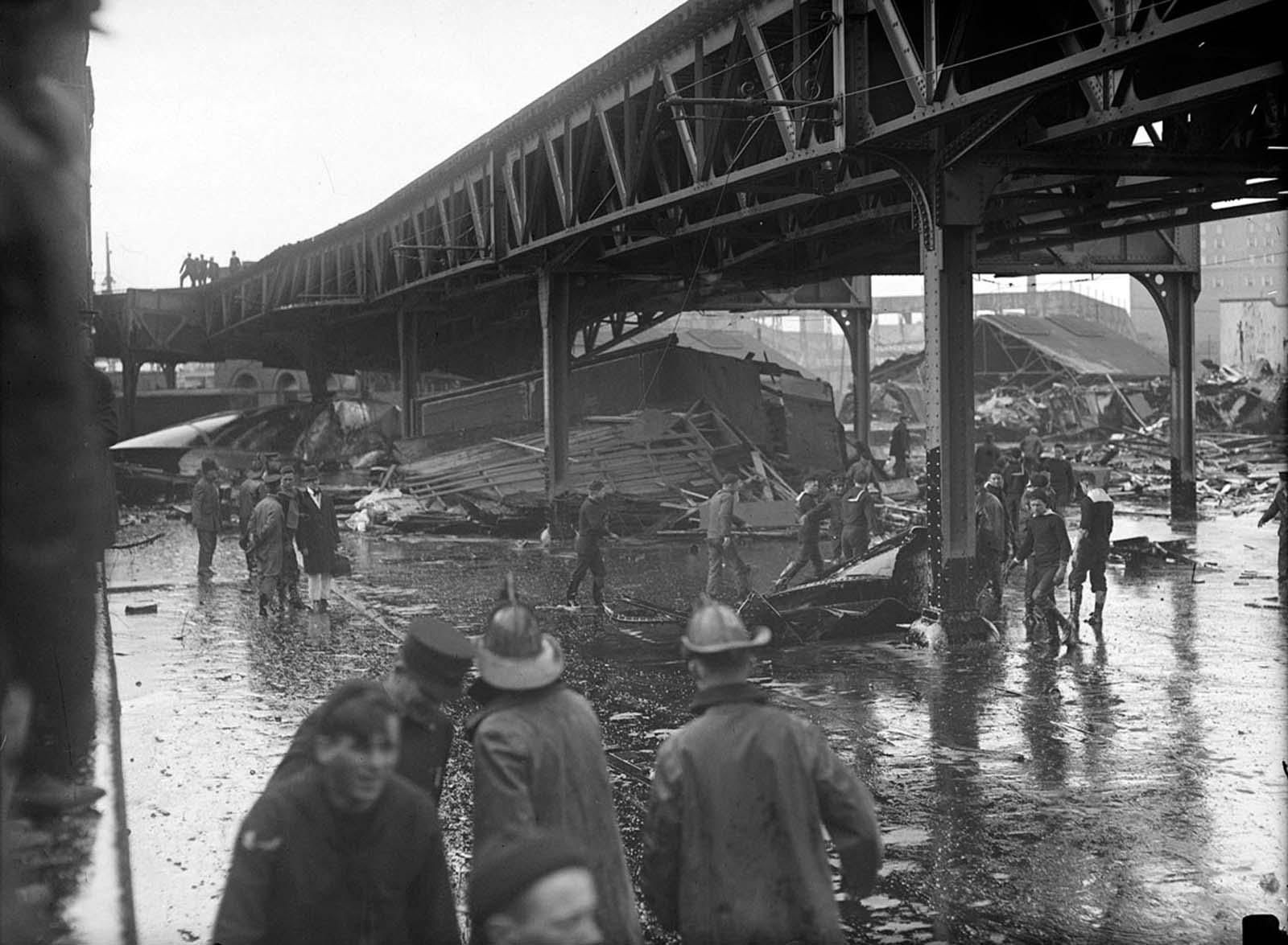 Firefighters and others stand in a pool of molasses after the explosion of a molasses storage tank owned by the United States Industrial Alcohol Company in Boston on January 15, 1919. About 2.3 million gallons of molasses flooded the area, killing 21 people, injuring 150, trapping a dozen horses, and destroying buildings, homes and part of the elevated train.