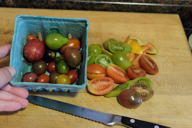 A half quart of heirloom cherry tomatoes to the left, a knife, and the rest of the quart of tomatoes halved to the right.