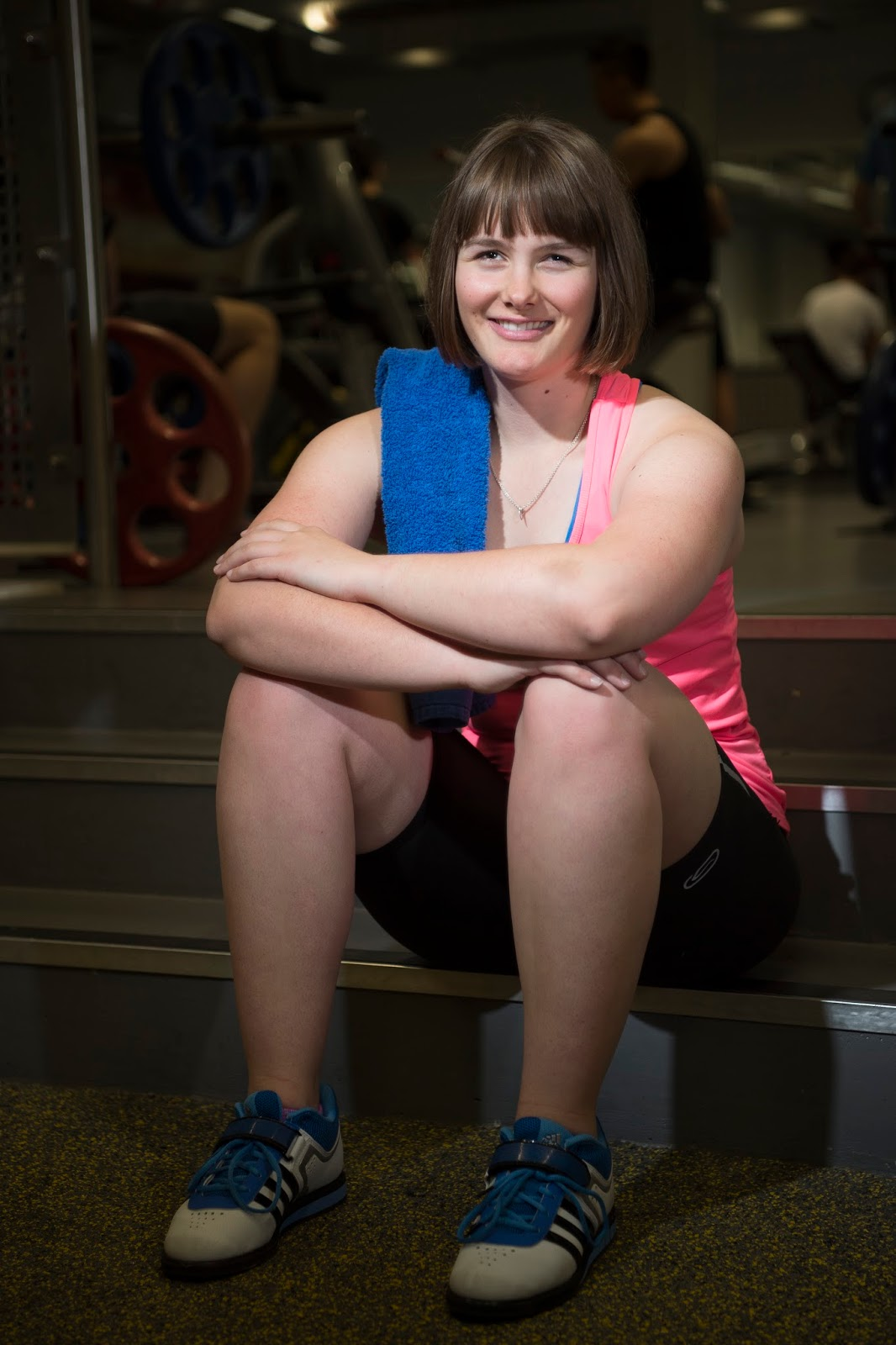 Photo of Millie smiling, sitting down wearing sports clothing and trainers, a towel is hung over one shoulder