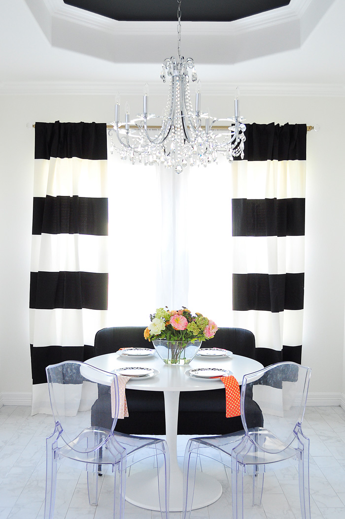 Black and white striped curtains in a small dining area with a tulip dining table and lucite ghost chairs. | via monicawantsit.com