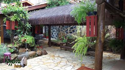 Entre a área do restaurante e os sanitários o quiosque de piaçava com o laguinho de carpas com a bica d'água no pote de barro com a parede de pedra e o piso com cacos de pedra São Tomé.