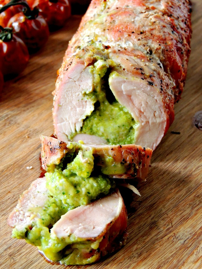 Broccoli Pesto and Cheese Stuffed Grilled Pork Tenderloin on a wooden cutting board with grilled cherry tomatoes.