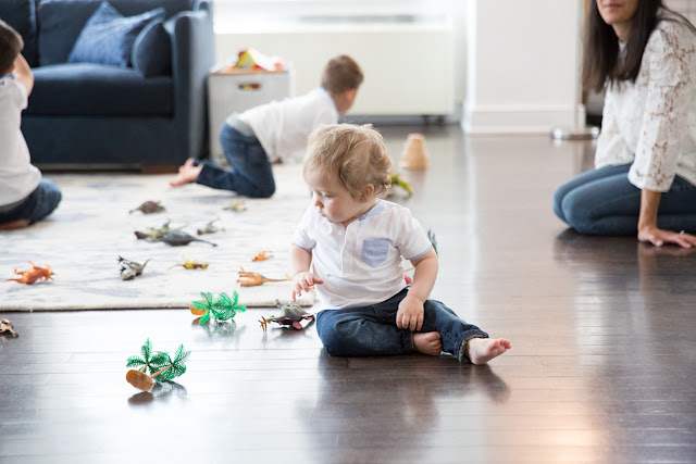youngest son plays on the floor during family portraits while mom watches