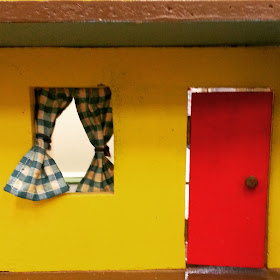 Vintage dolls' house front door and window with green gingham curtain.