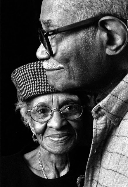 Beautiful black and white photo of an old black couple hugging each other. Both wearing glasses.
