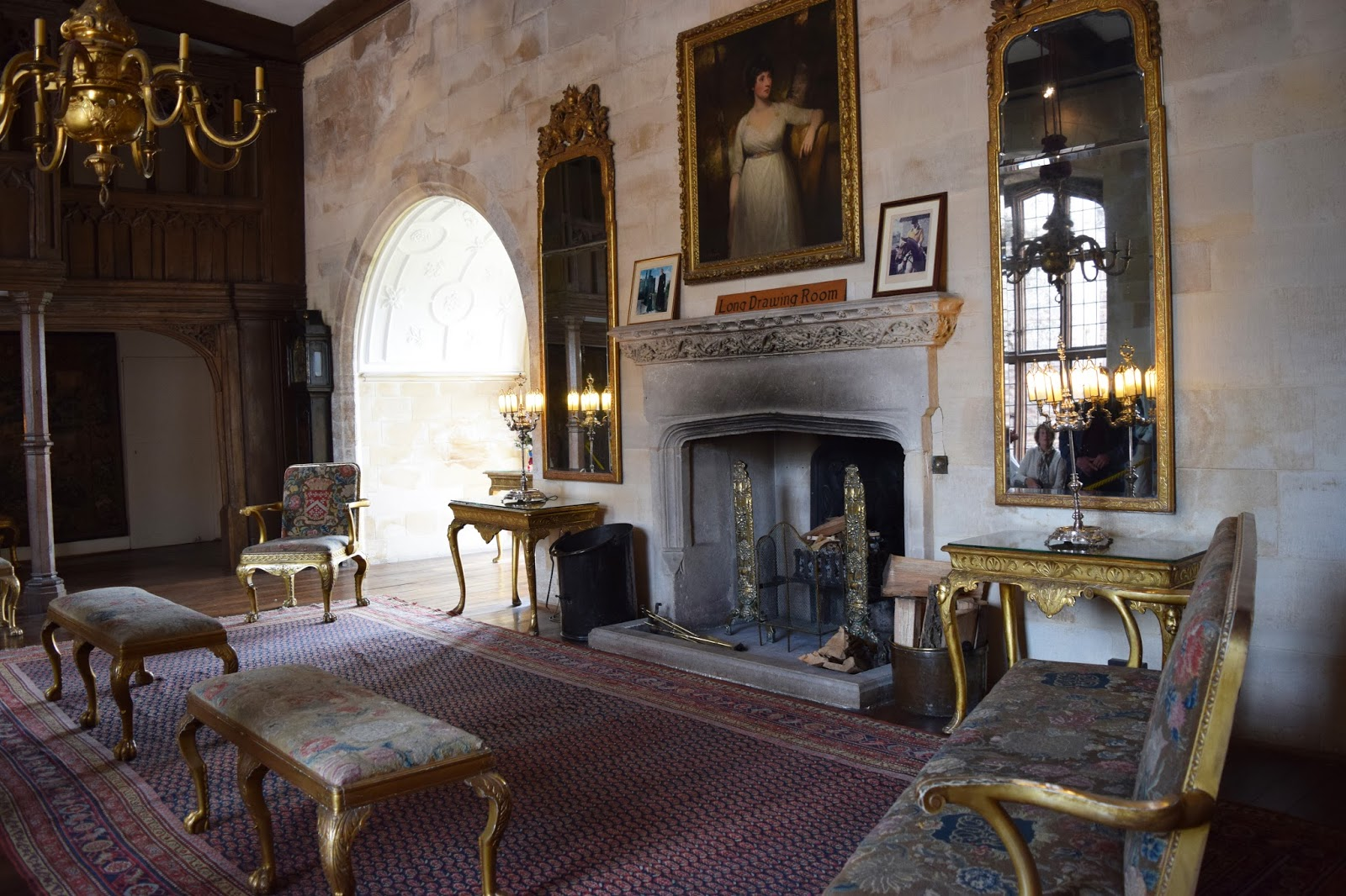 the main hall inside Berkeley Castle. A large fireplace is the main focus of the room. In front of the fireplace is a large red rug. Golden chairs are places about the edges of this rug