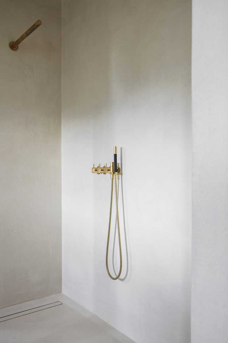 Shower with brass fixtures. Interior design by Arjaan De Feyter, photo by Piet-Albert Goethals