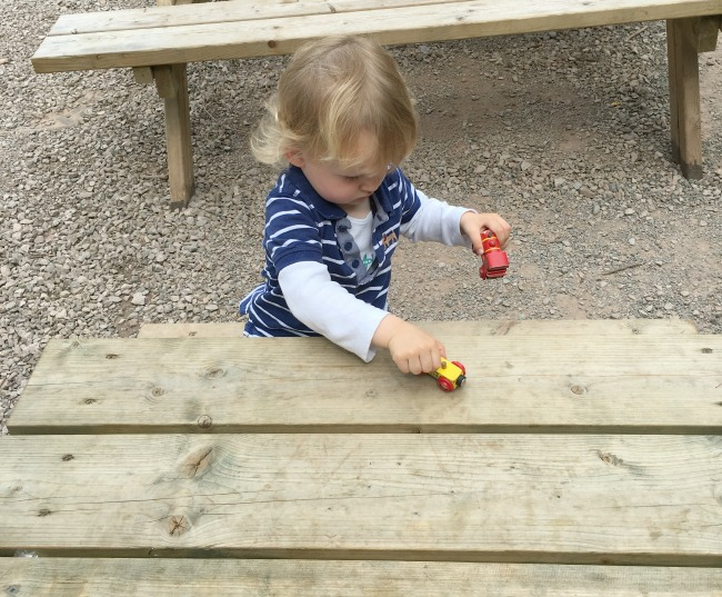 toddler-on-picnic-bench-with-wooden-train