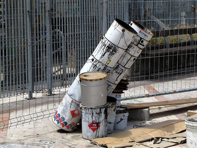Leaning pile of empty paint drums, piazza Attias, Livorno