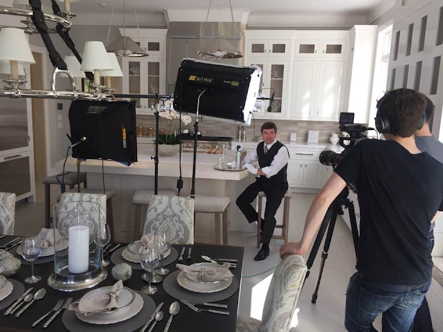 butler being filmed demonstrating a cleaning product in a large white upscale kitchen