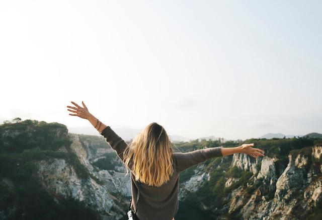 Mulher de braços aberto a olhar o horizonte