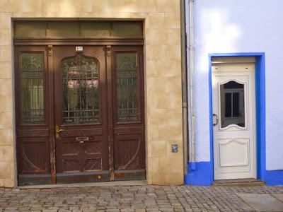 Schöne alte Tür neben neuer hässlicher aus Plastik