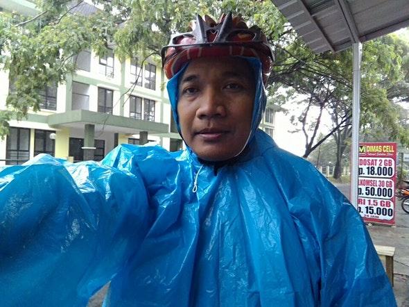 Bersepeda ketika musim hujan harus siap membawa jas hutan plastik.