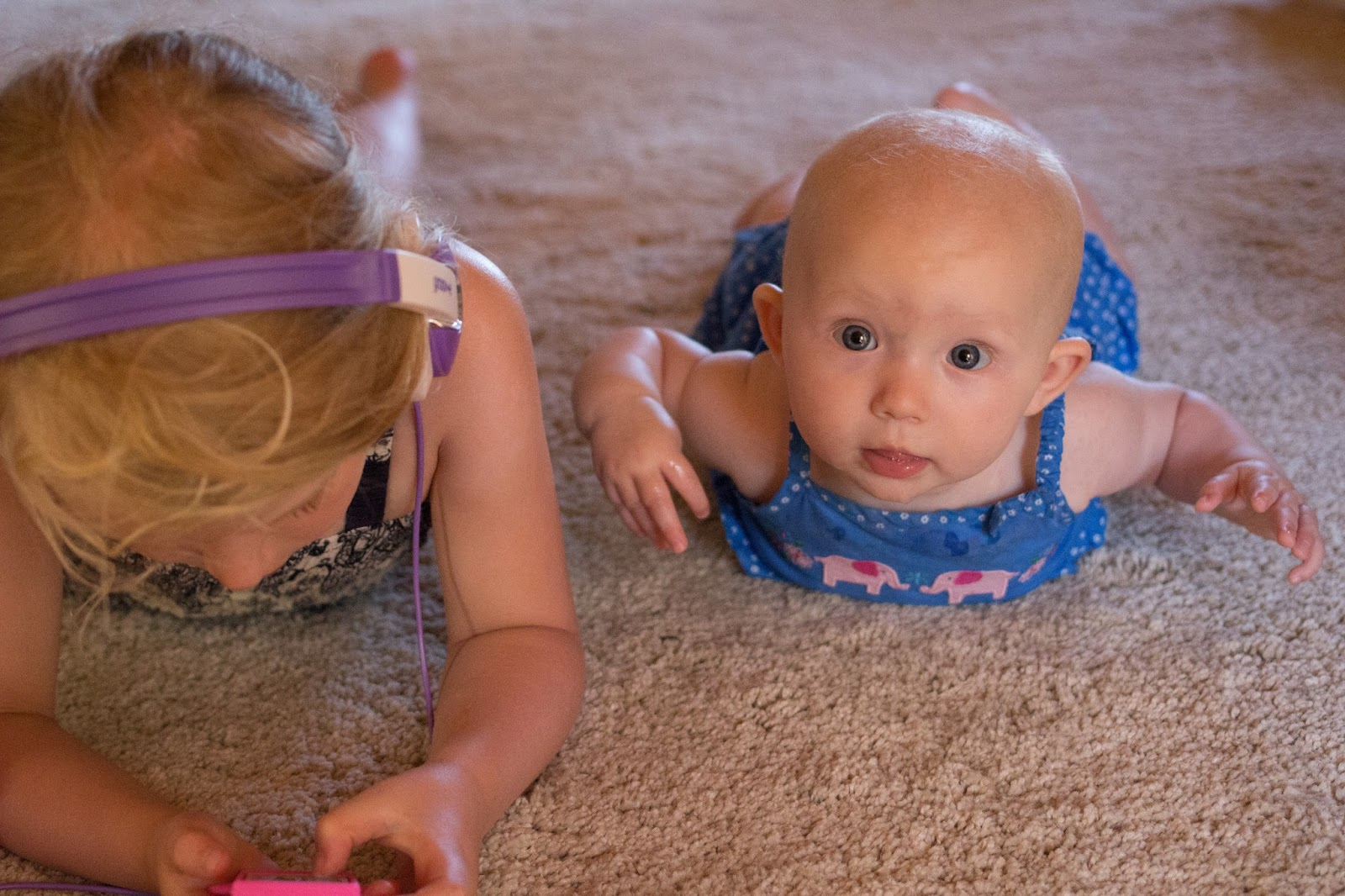 Baby lying on her tummy looking at the camera next to a little girl lying on her tummy listening to music on an ipod