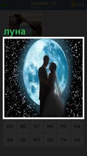на фоне полной луны обнимаются мужчина с женщиной