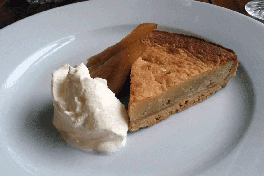 Frangipane and pear tart, with poached pear and cream.