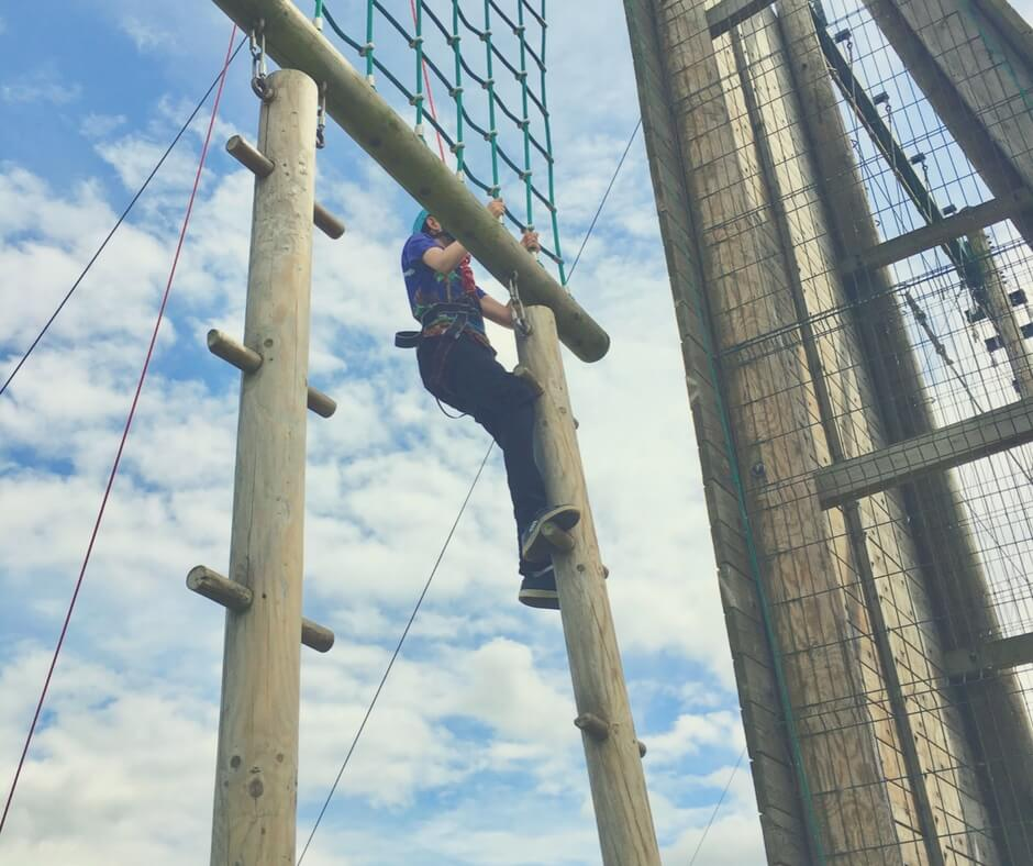 A 13 year old boy climbs up a rope ladder. His hands cling to the green rope, his knuckles white. His shoes bend as he steps onto the rope. A red rope connected to his harness keeps him from falling. He also wears a green helmet. The sky behind him is dotted with fluffy white clouds.