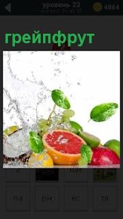 В разрезанном виде грейпфрут с брызгами воды сверху на него