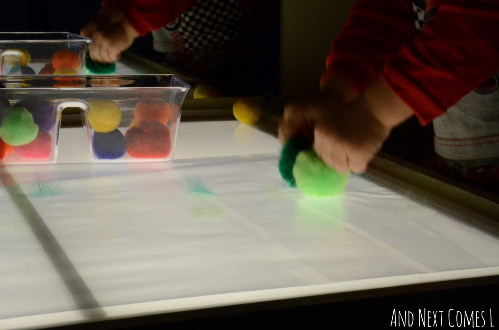 Creating art with pom poms on the light table from And Next Comes L