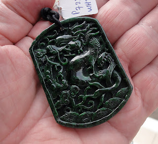 black jadeite pendant with mythical carvings