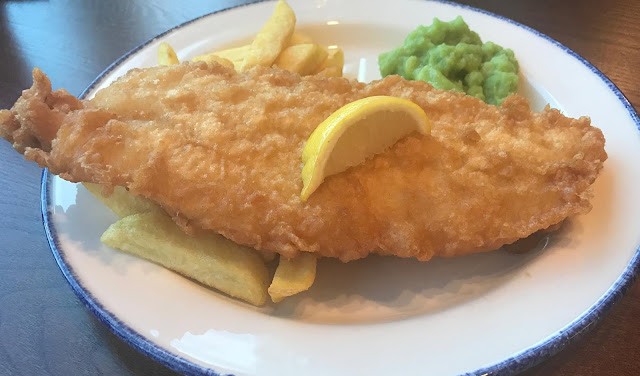 battered cod and chips with slice lemon and mushy peas