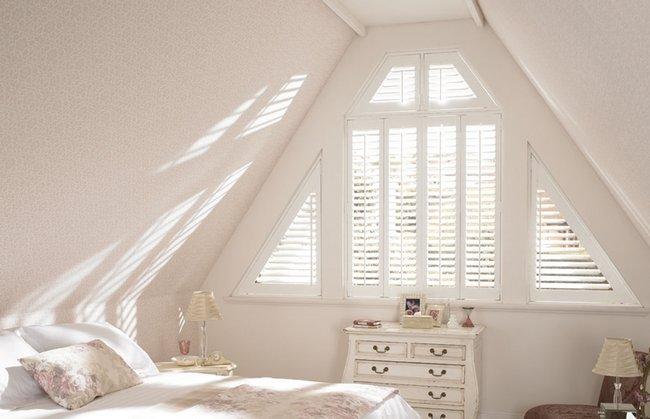 Białe okiennice wewnętrzne w sypialni w kształcie trójkątka