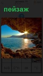 Нависший камень образует арку с видом на голубое море и солнечные лучи, которые попадают внутрь образуя красивый пейзаж