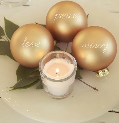 Christmas gold ball ornaments with love, peace, and mercy printed and candle by Hello Lovely Studio