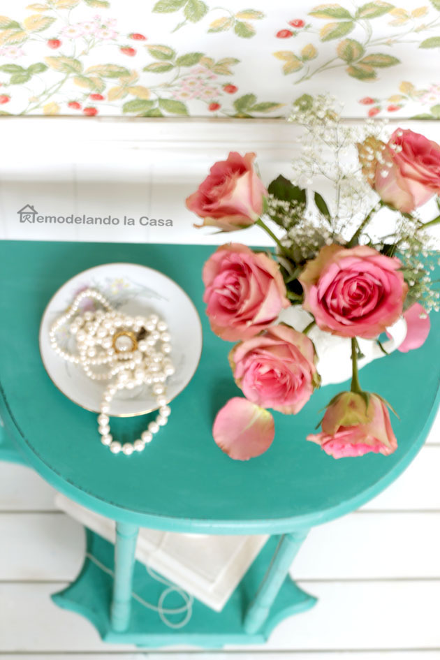 pink roses in white pitcher, white floor, white pearls in saucer on table