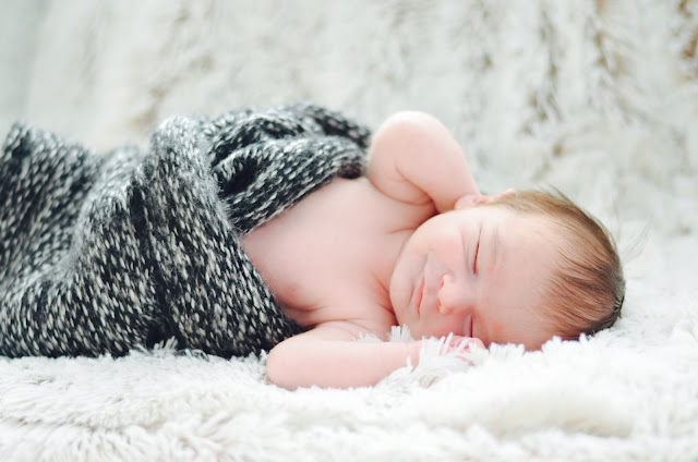 newborn snuggled in fluffy throw photography