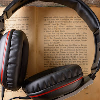 A pair of chunky over-ear headphones rest on an old book.
